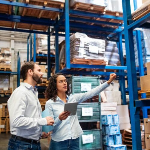 Businesswoman with a digital tablet showing and talking with male worker in distribution warehouse. Manager working with foreman in warehouse checking stock levels.